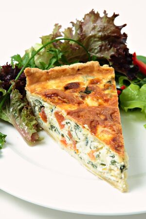 A delicious quiche made from spinach beet (aka Swiss chard or sea kale beet), leek and tomato, served with a garden fresh salad. Stock Photo - 12437372