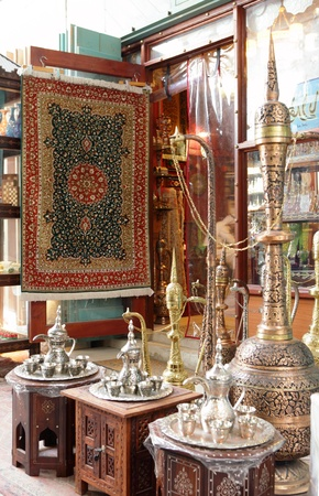 inlaid: A shop display of traditional metal ornamental  coffee pots and inlaid tables in an arcade in Souq Waqif, Doha, Qatar
