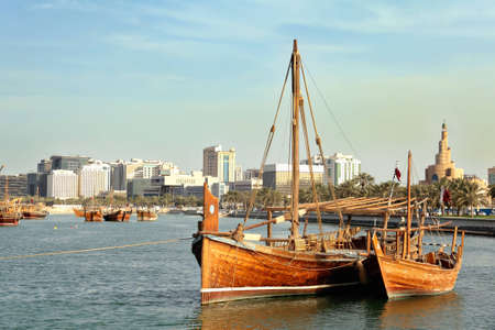 persian gulf: A jalibut dhow, with its distinctive vertical prow, tied up next to a smaller traditional boat - possibly a zaruq - in front of the landmark spiral mosque in Doha, Qatar Stock Photo