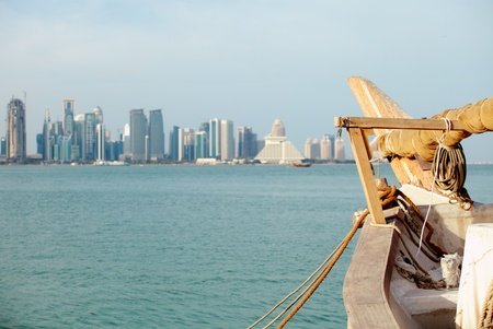 prow: The prow of a sailing dhow in Doha, Qatar, with the city Stock Photo