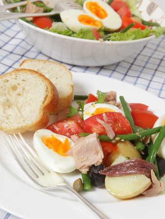 A meal of traditional nicoise salad - lettuce, potato, tomato, green beans, tuna, anchovies, boiled eggs, capers, black olives and a garlic vinegrette and garnished with flat-leaf parsley - served with slices of French bread photo