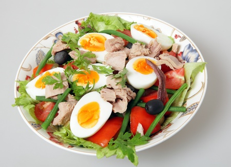 A serving bowl of freshly made traditional nicoise salad - lettuce, potato, tomato, green beans, tuna, anchovies, boiled eggs, capers and black olives, garnished with flat-leaf parsley, over a neutral grey background