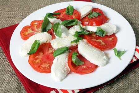 caprese salad: A traditional italian caprese salad of bufala mozzarella cheese, tomatoes and basil. The colours reflect the flag of Italy