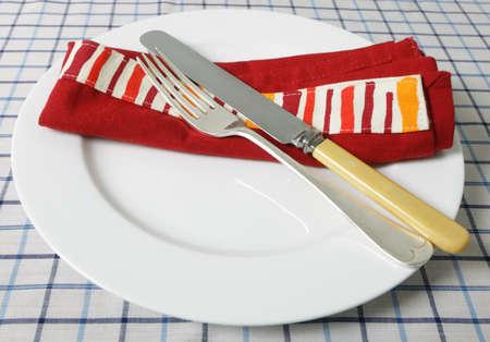 servilleta de papel: Placa con los cubiertos y la servilleta retro en una mesa Foto de archivo