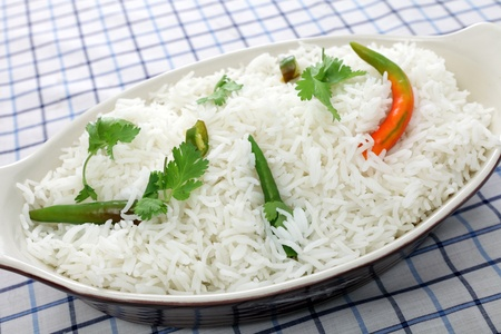 A bowl of basmati rice garnished with coriander (cilantro) and hot chillis, to go with a spicy Asian meal
