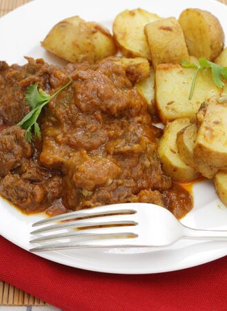beef curry: A madras butter beef curry served with curried potatoes and garnished with coriander leaves