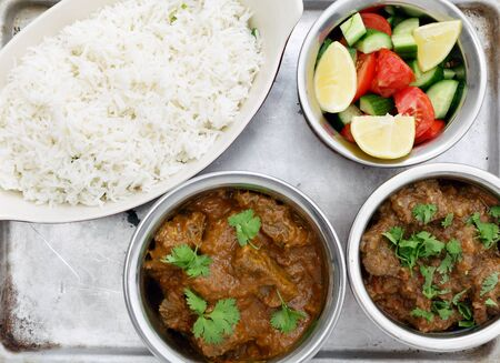 beef curry: High angle view of a Madras butter beef curry (centre bottom) and ordinary curried beef with salad and rice, on an aluminium tray seen from above