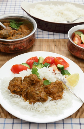 beef curry: A plate of Madras butter beef curry with rice, salad and serving dishes in the background