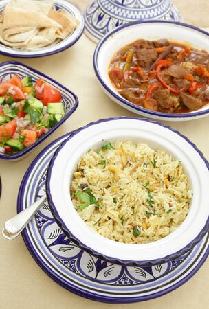 comprising: A table set for a Moroccan meal, comprising rice with nuts and onion, a tomato, cucumber and capiscum tossed salad and a spicy beef tagine stew Stock Photo