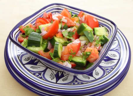 moroccan cuisine: A moroccan salad of tomato, cucumber, onion and coriander  cilantro  leaves tossed in olive oil and vinegar and finished with lemon juice Stock Photo