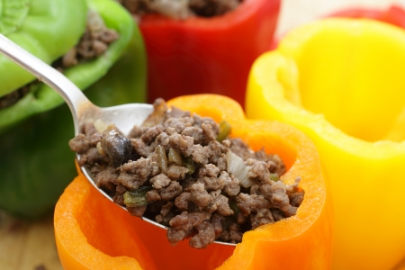Colourful bell peppers or capsicums being stuffed with a filling of ground beef, mushroom, onion and celery  photo