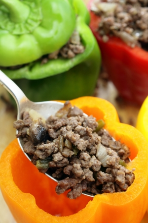 ground beef: Colourful bell peppers or capsicums being stuffed with a filling of ground beef, mushroom, onion and celery