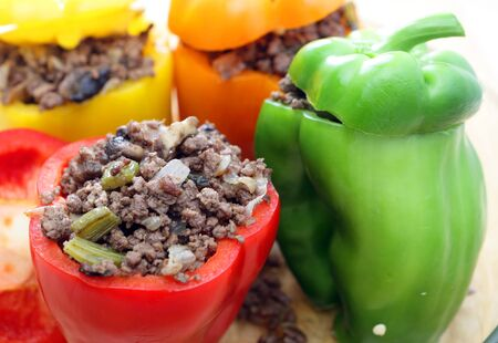 Colourful bell peppers or capsicums stuffed with a filling of ground beef, mushroom, onion and celery and ready for the oven photo