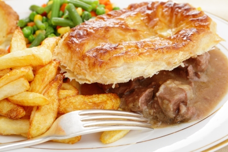 A meal of a homemade steak and kidney pie with french fried potato chips and mixed vegetables Stock Photo