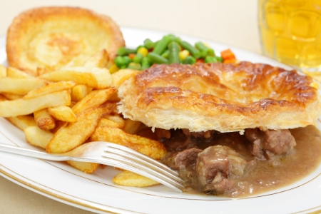 A meal of a homemade steak and kidney pie with french fried potato chips,yorkshire pudding and mixed vegetables photo