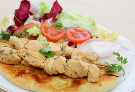 chicken kebab: Chicken tikka skewers served on homemade Naan flatbread with a salad