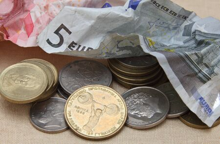 replaced: Crumpled euro banknotes are pushed aside to make way for a return of Greek drachma coins