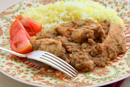 chicken rice: A plate of chicken and lentil curry, chicken dhansak, served with yellow and white rice and tomato