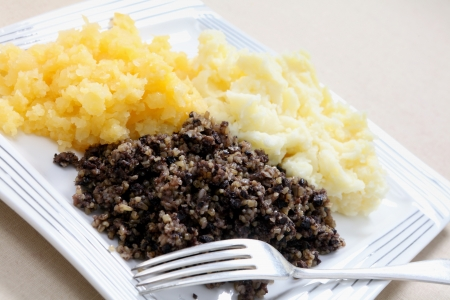 burns night: A traditional Scottish haggis meal, often served on Burns Night, with mashed potatoes and swede also known as tatties and neeps.