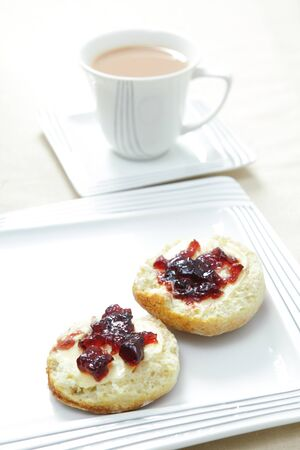 british food: A traditional English afternoon tea of a scone topped with butter and blackcurrant jam and a cup of milky tea.