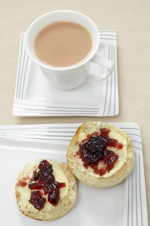 scone: A traditional English afternoon tea of a scone topped with butter and blackcurrant jam and a cup of milky tea.