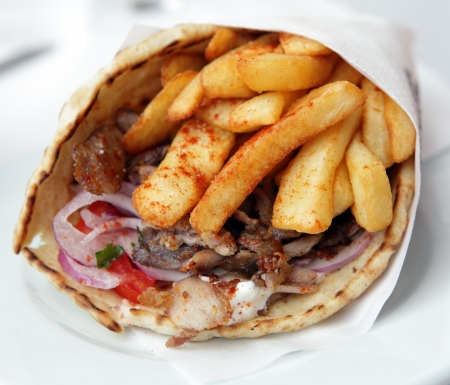View of a pork souvlaki wrap, or pitta gyros,  incorporating fries, yoghurt and a salad or onion, tomato and parsley Stock Photo