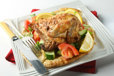 kosher: Mid-east style barbecue chicken  Originally an Egyptian dish but now very popular in Israel and other parts of the Middle East, the chicken is marinaded in lemon and spices and served  with coriander leaves on a salad and pitta bread