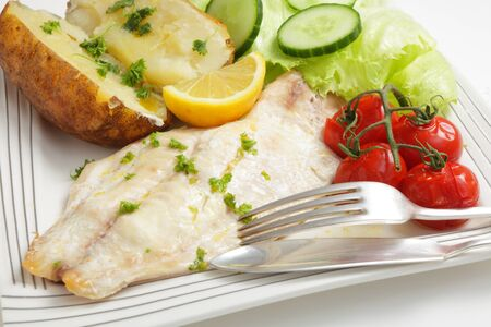 russet potato: Close-up on an oven baked white fish fillet served with baked potato and tomatoes, a wedge of lemon and a lettuce and cucumber salad Stock Photo
