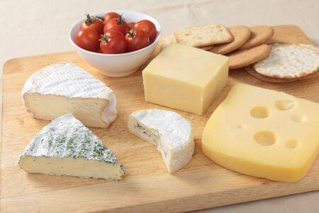 tabla de quesos: Una tabla de quesos con Jarlsberg, Cheddar, Brie hierbas, quesos Camembert y St Albry, un plato de tomates cherry y algunas galletas Foto de archivo