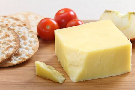 cheddar cheese: A wedge of English Cheddar cheese with crackers and cherry tomatoes on a cheeseboard