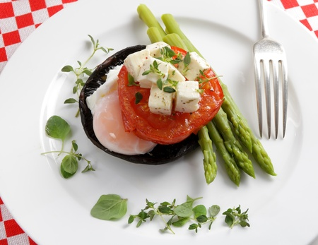 An appetizer of grilled portobello mushroom topped with a poached egg, grilled tomato slice and asparagus spears, all topped with marinaded feta and a herb garnish