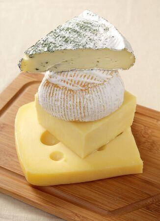 tabla de quesos: Una pila de quesos europeos, desde lo alto, Brie con las hierbas, St Albry, ambos de Francia, Jarlsberg danés y cheddar Inglés Foto de archivo