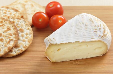 cheeseboard: A wedge of St Albry cheese with crackers and cherry tomatoes on a cheeseboard Stock Photo