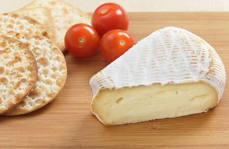 tabla de quesos: Una cu�a de queso Albry St con galletas y tomates cherry en una tabla de quesos