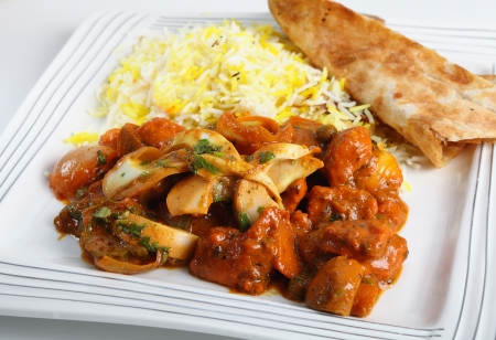 pakistani food: Chicken jalfrezi curry on a plate with pilau rice and a piece of naan bread. Stock Photo