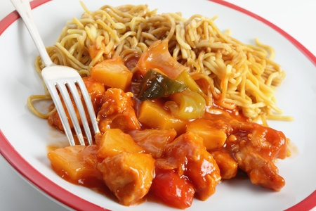 Chicken sweet and sour on a plate with chinese noodles and a fork photo