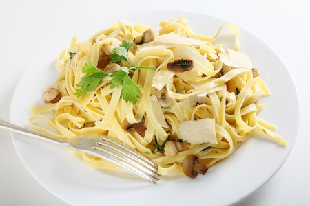 AI: Ribbon pasta with mushrooms and italian parsley, fettuccine ai funghi, topped with curls of parmesan reggiano and with a fork