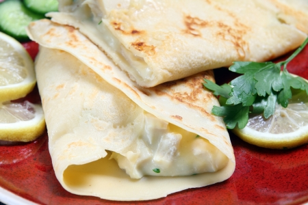crepes: Crepe filled with chicken in white sauce, served with slices of lemon and cucumber.