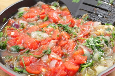 fryingpan: Fried o nion and parsley and tomatoes in a pan, part of the preparation for a greek stuffed aubergine dish