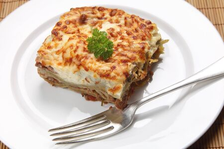 verdi: A slice of homemade lasagne verdi on a plate with a fork, high angle view Stock Photo