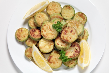 sautee: Sauteed courgette (zucchini) slices served with lemon wedges and garnished with parsley viewed from above Stock Photo
