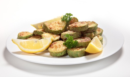 sautee: Sauteed courgette (zucchini) slices served with lemon wedges and garnished with parsley. The the courgettes are sliced, tossed in flour and fried in butter or olive oil and then seasoned. Stock Photo