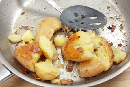 sautee: A frying pan with crushed potatoes cooked in butter and olive oil with some garlic