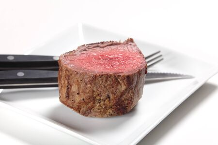 peppered: A chateaubriand or tenderloin steak on a plate with a steak knife and fork