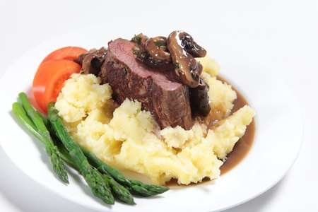 plated: Chateaubriand beef tenderloin steak topped with a mushroom gravy sauce served on a bed of potato with asparagus and slices of tomato. Stock Photo
