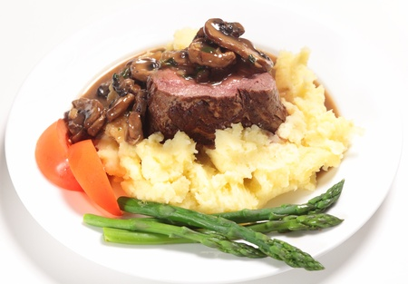 plated: Chateaubriand beef tenderloin steak topped with a mushroom sauce served on a bed of potato with asparagus and slices of tomato.