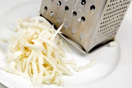 queso rallado: queso de cabra después de su transformación a través de un rallador de queso Foto de archivo