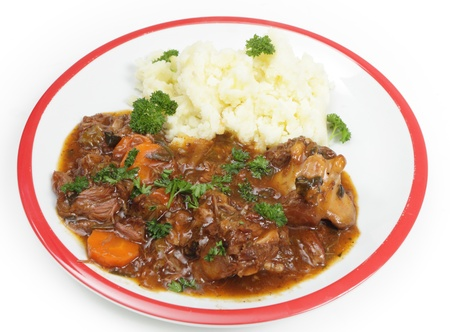 beef stew: A plate of old-fashioned oxtail stew, served with mashed potato and garnished with Englush parsley