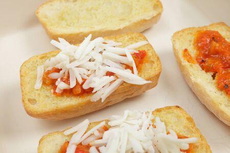 queso rallado: Rebanadas de pan tostado ciabatta, rematado con un margen comercial y bruschetta con queso rallado espolvoreado por encima de ellos, casi listo para tostar en la parrilla Foto de archivo