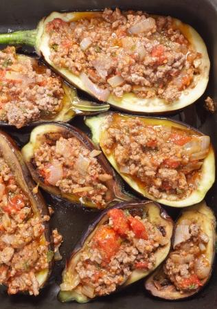 carne picada: Berenjena o berenjenas rellenas con una salsa de carne picada, el tomate, la cebolla y el perejil en la preparación del plato griego melitzanes papoutsakia Foto de archivo